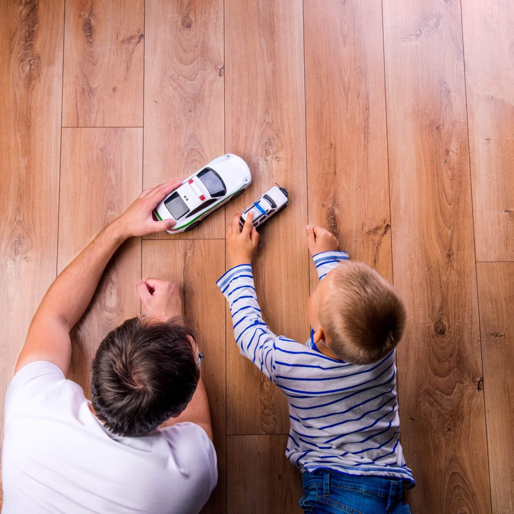 Father and kid playing with toycars on Hardwood floor | Bram Flooring